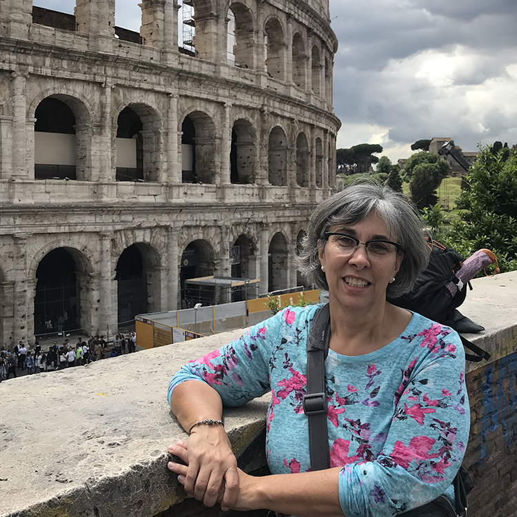 white female smiling, with Roman Colosseum in the background