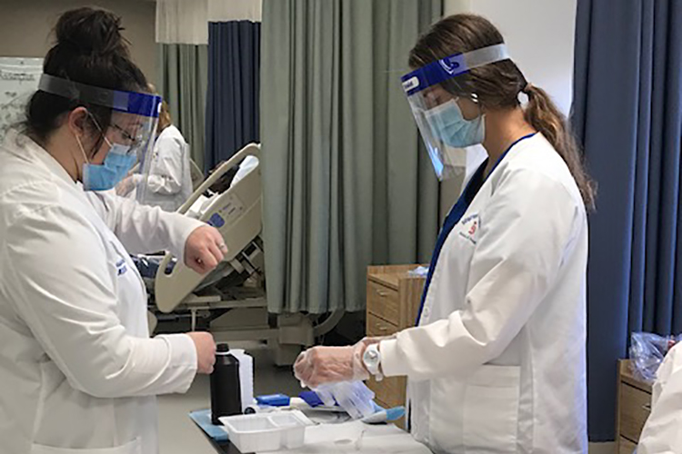 clinical professor assisting nursing student in simulation lab
