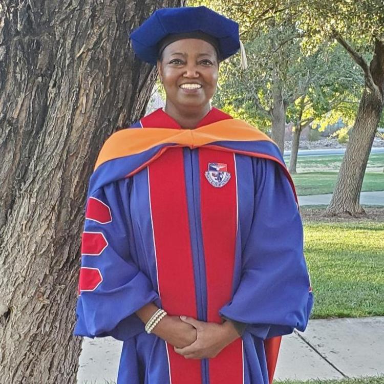 Black woman dressed in graduation robe