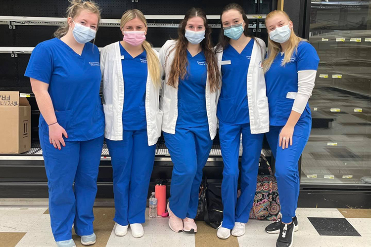 Group of female nursing students, wearing blue scrubs, posing for camera
