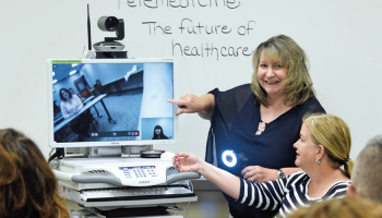 woman demonstrates telehealth cart in front of classroom