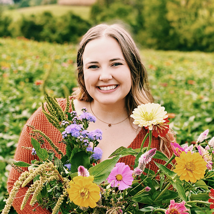 Smiling young woman poses in a field of flowers