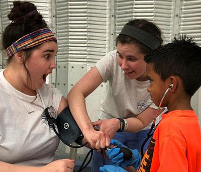 young boy listens through stethoscope