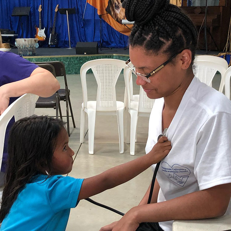 young Costa Rican girl holds stethoscope up to chest of American nursing student