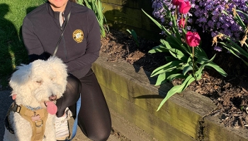woman and dog pose in front of flowers