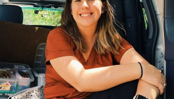 woman, sitting in back of a van, posing and smiling for camera