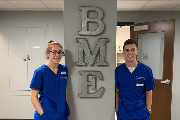 Two BME/BSN students in blue scrubs pose for camera