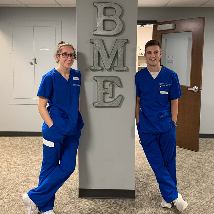 female and male nursing students in blue scrubs pose in hallway