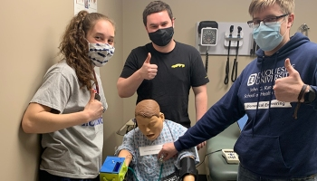three students pose with health care device and mannequin