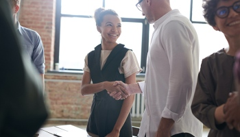 young woman shaking hands with older man in professional business setting